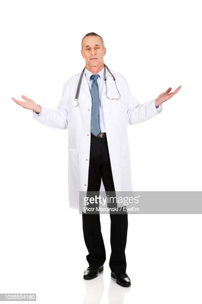 portrait of doctor wearing lab coat standing against white background - 白衣 ストックフォトと画像