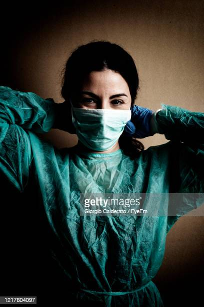 portrait of doctor wearing mask against wall - coronavirus doctor stock pictures, royalty-free photos & images