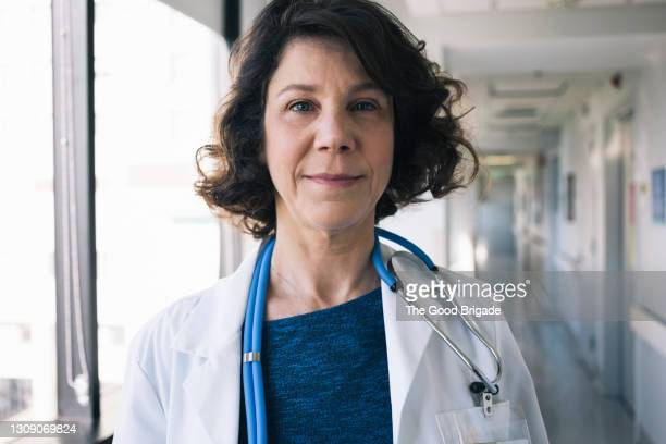 portrait of doctor with stethoscope in hospital corridor - focus on foreground stock pictures, royalty-free photos & images