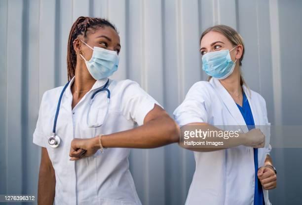 portrait of doctors with face mask greeting with elbow bump, coronavirus concept. - éviter de se serrer la main photos et images de collection