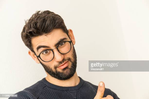 portrait of doubting young man with beard and glasses - 首をかしげる ストックフォトと画像