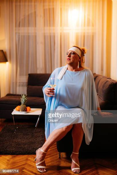Portrait of drag queen in blue dress and high heels - transsexual person at home