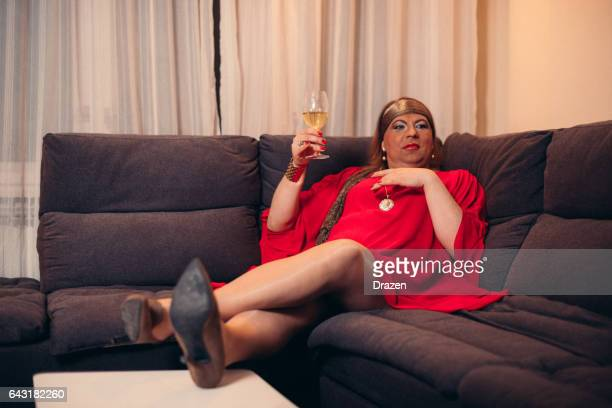 8b8e545650 Portrait of drag queen in red dress and high heels - transsexual person at  home