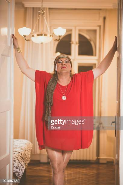 Portrait of drag queen in red dress and high heels - transsexual person at home
