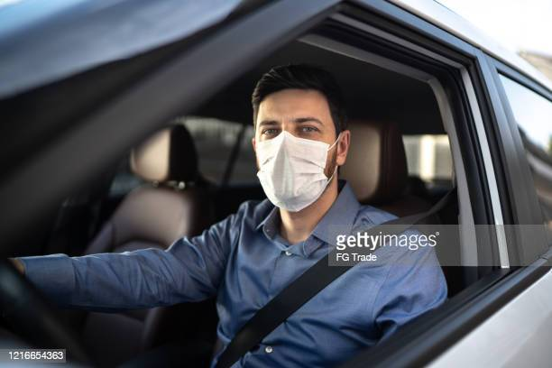 portrait of driver wearing protective medical mask - driver stock pictures, royalty-free photos & images