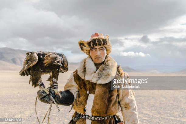 portrait of eagle hunter standing in desert in mongolia - independent mongolia stock pictures, royalty-free photos & images