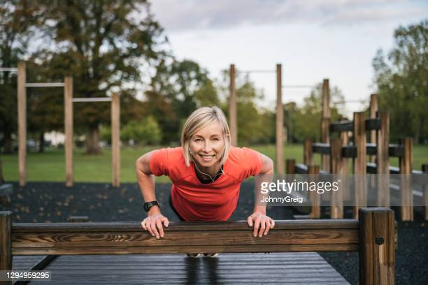 portrait of early 50s female athlete doing incline push-ups - clapham common stock pictures, royalty-free photos & images