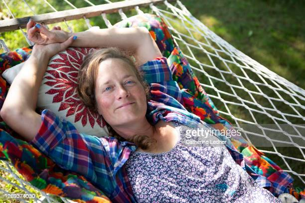 portrait of earthy blue eyed woman lying in the shad in a hammock in rural maine - catherine ledner stock pictures, royalty-free photos & images