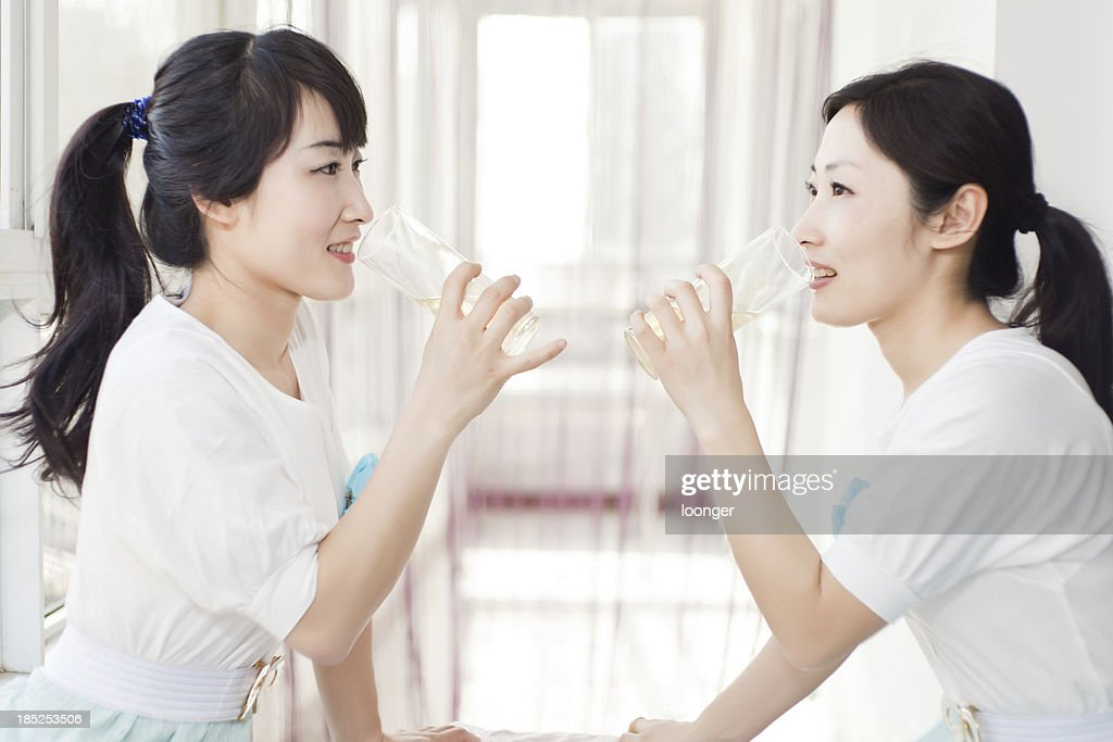 portrait of east asian twins drinking water : Stock Photo