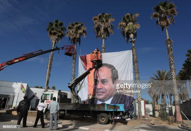 A portrait of Egyptian President Abdel Fattah alSisi hangs the Rafah border crossing with Egypt on November 1 2017 Hamas handed over control of the...