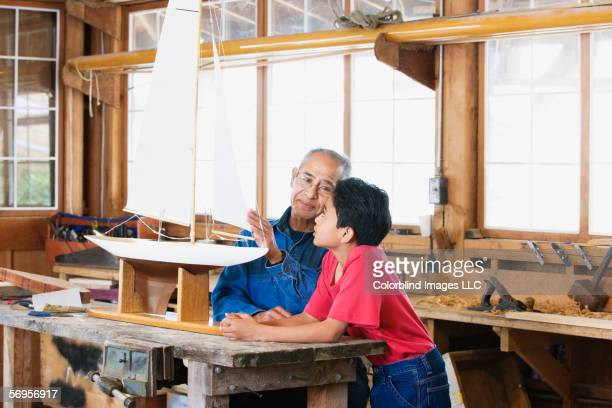 portrait of elderly man and boy with model sailboat - model building stock photos and pictures