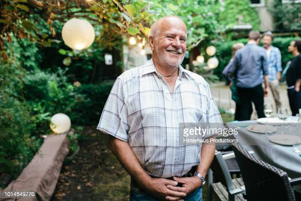 portrait of elderly man during family meal - senior stock-fotos und bilder