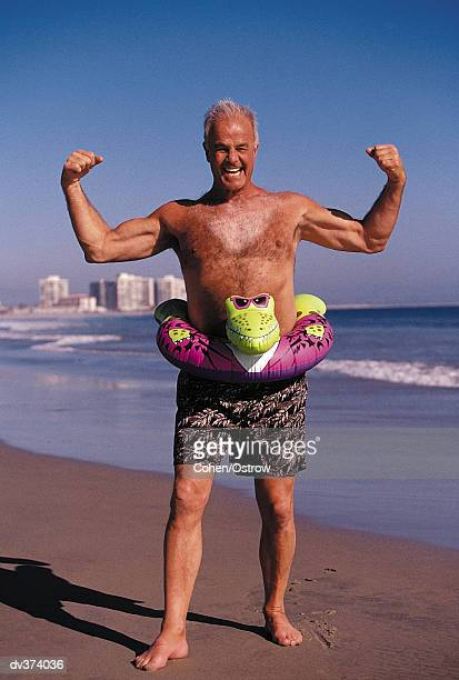 Portrait of elderly man flexing on beach
