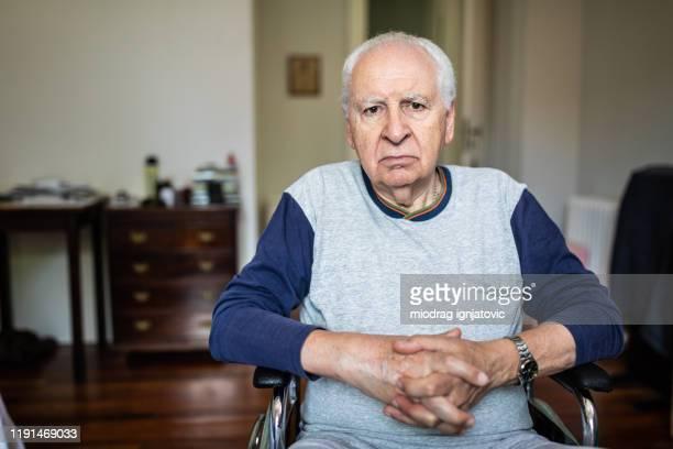 portret van een oudere man in een rolstoel thuis - alleen seniore mannen stockfoto's en -beelden