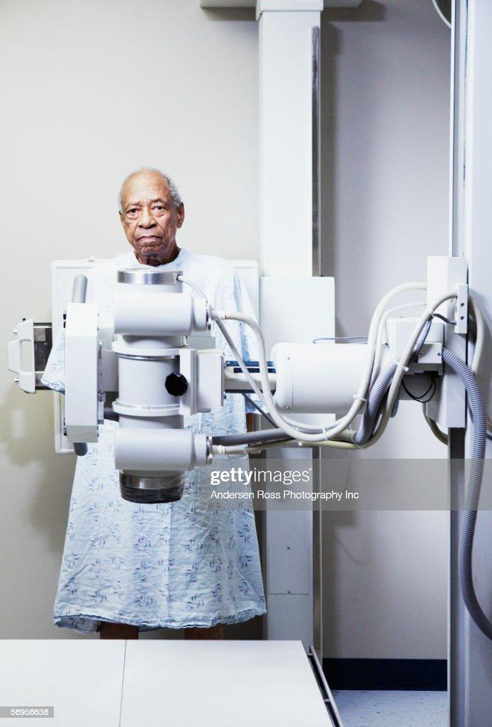 Portrait Of Elderly Man In Gown Behind Xray Machine Stock Photo ...