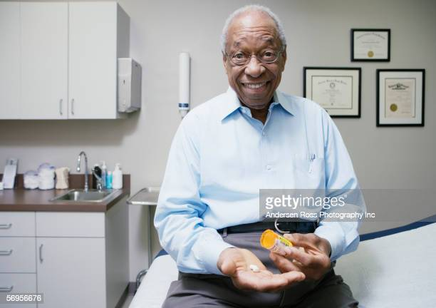 portrait of elderly man sitting in clinic taking medication - examination table stock pictures, royalty-free photos & images