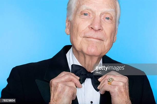Portrait of elderly man straightening bowtie