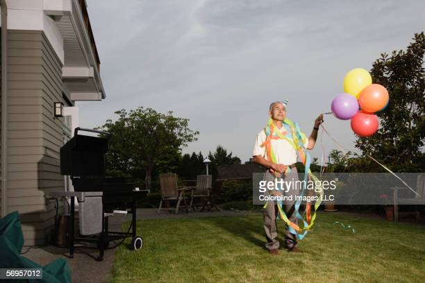 portrait of elderly man wearing birthday hat and streamers and holding balloons - funny bbq stock pictures, royalty-free photos & images