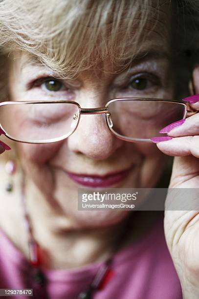 Portrait of elderly woman adjusting reading glasses