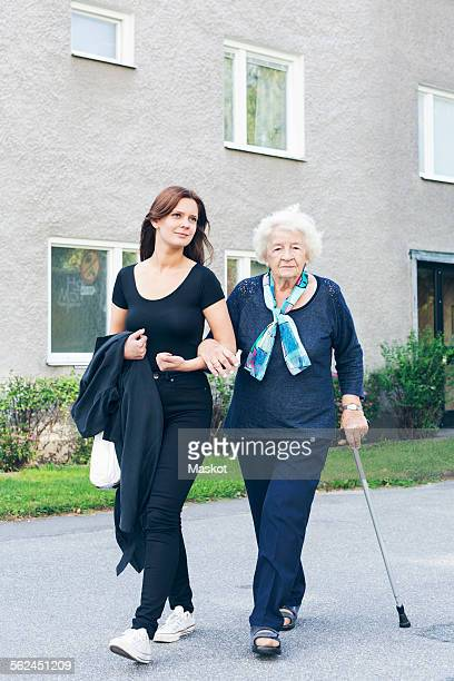 Portrait of elderly woman holding cane while walking with granddaughter on footpath against building