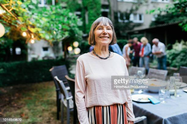 portrait of elderly woman smiling after bbq - alter erwachsener stock-fotos und bilder