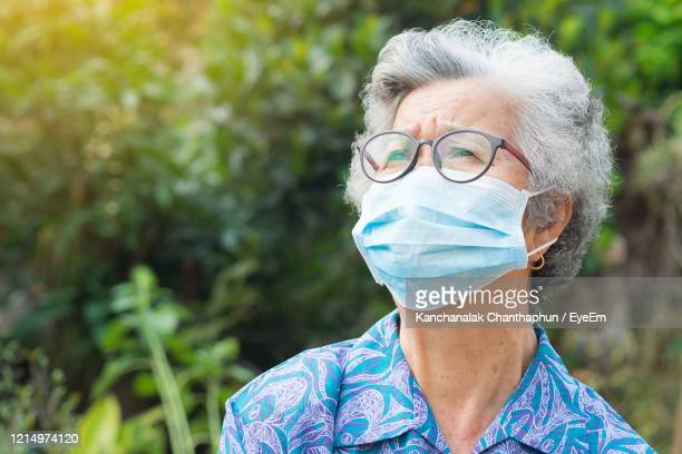 portrait of elderly woman wearing mask standing and looking up in garden. - senior women stock pictures, royalty-free photos & images