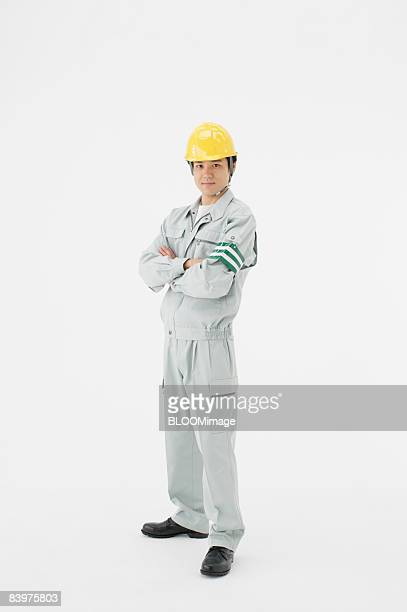 portrait of electrician with arms folded, studio shot - ヘルメット ストックフォトと画像