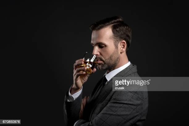 Porträt von eleganten Mann trinken whiskey