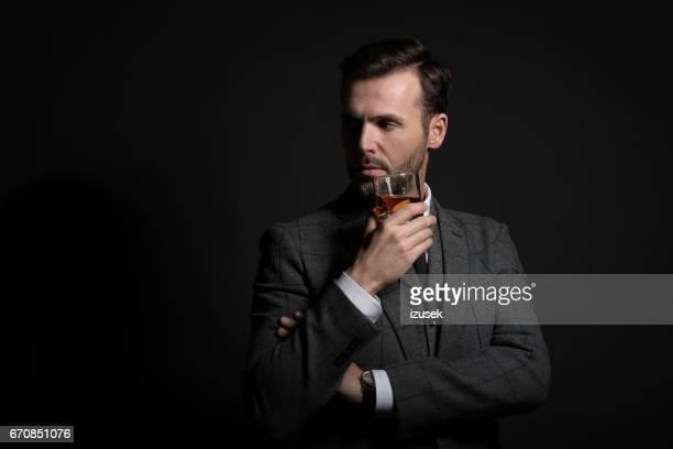 Portrait of elegant man drinking whiskey