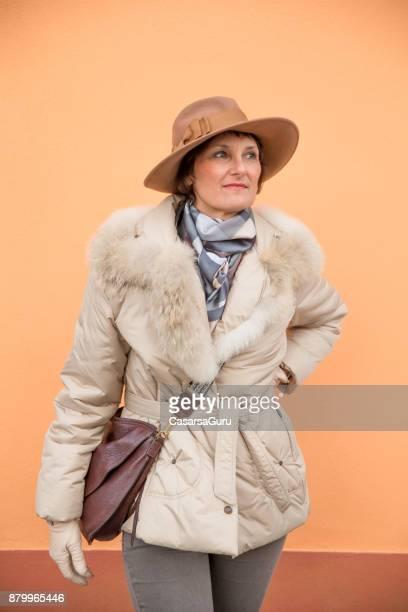 Portret van elegante volwassen vrouw voor oranje achtergrond
