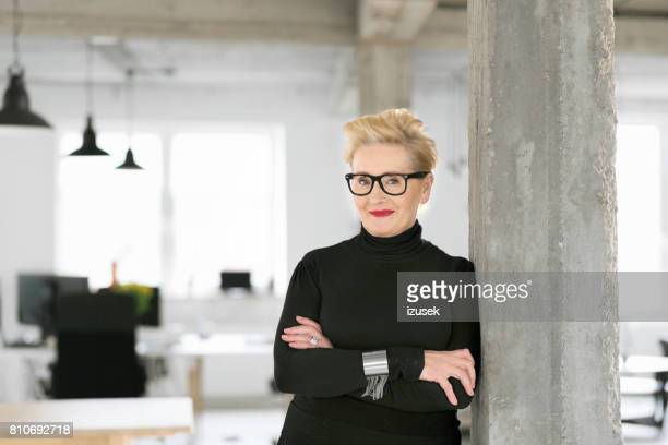 portrait of elegant senior businesswoman in the modern studio - business owner stock photos and pictures
