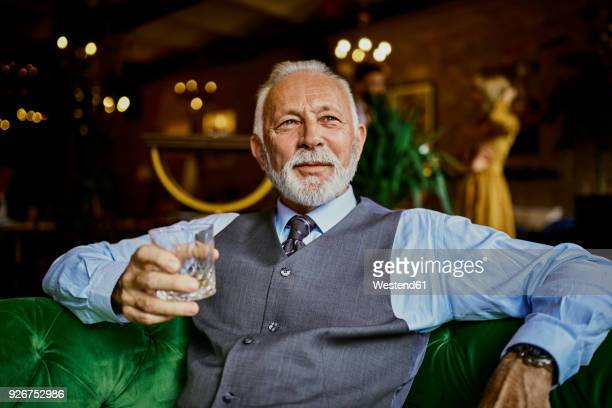 Portrait of elegant senior man sitting on couch in a bar holding tumbler