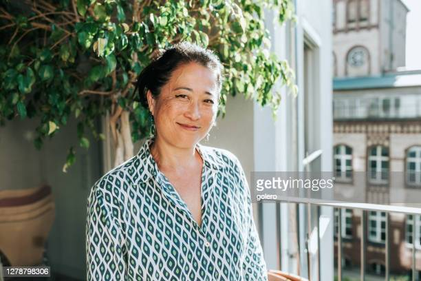portrait of elegant smiling woman at sunny balcony - mid adult stock pictures, royalty-free photos & images
