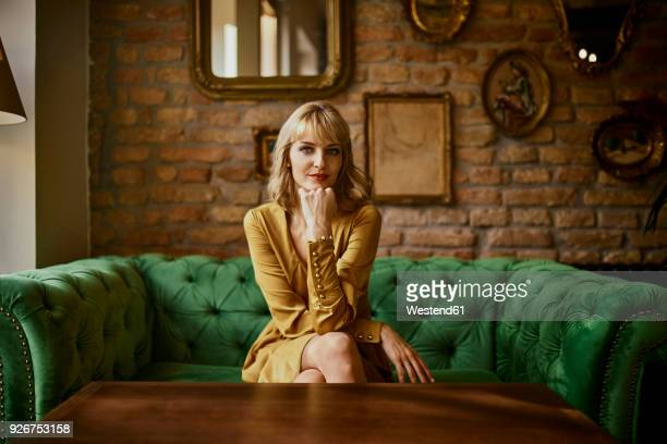 portrait of elegant woman sitting on a couch - elegantie stockfoto's en -beelden