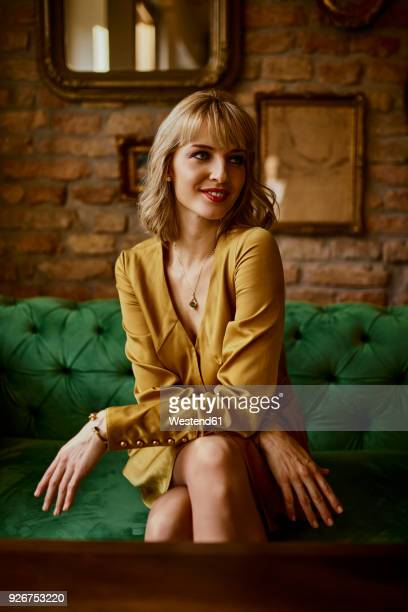 portrait of elegant woman sitting on a couch - versierde jurk stockfoto's en -beelden