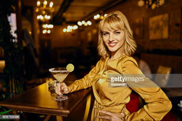 portrait of elegant woman with cocktail in a bar - elegante kleidung stock-fotos und bilder
