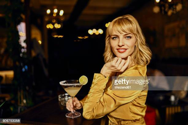 Portrait of elegant woman with cocktail in a bar