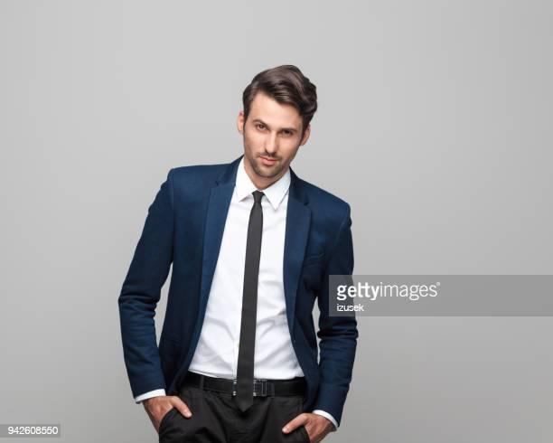 porträt von eleganten jungen mann im anzug - hände in den taschen stock-fotos und bilder