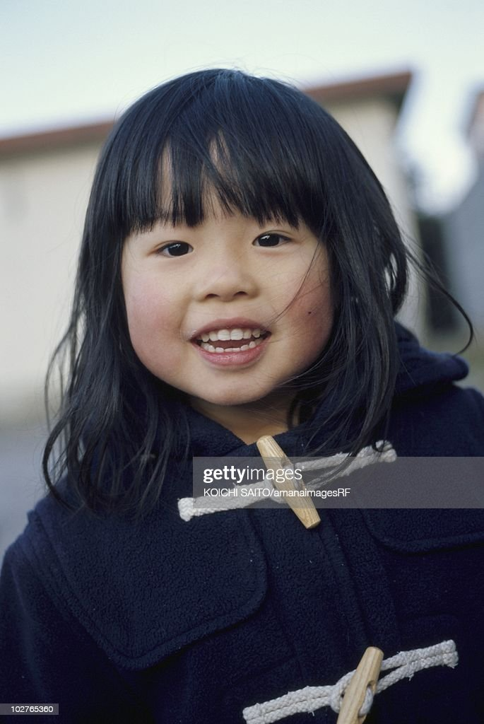 Portrait of elementary age girl in a duffle coat : ストックフォト