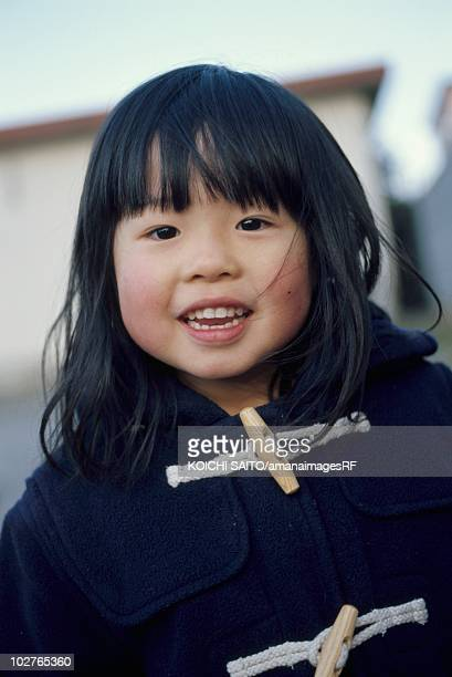 portrait of elementary age girl in a duffle coat - ダッフルコート ストックフォトと画像
