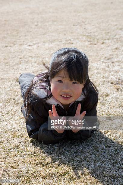 Portrait of elementary age girl lying in a field doing peace signs