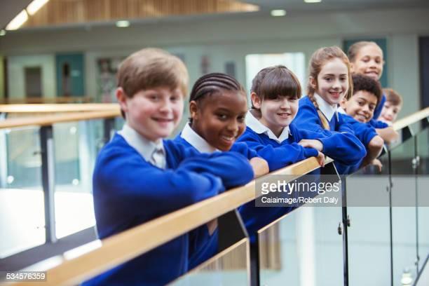 Portrait of elementary school children wearing blue school uniforms standing in school corridor