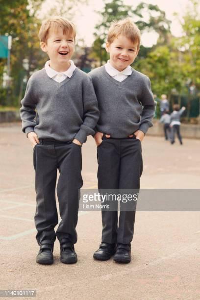 portrait of elementary schoolboy twins in playground - schulkind nur jungen stock-fotos und bilder