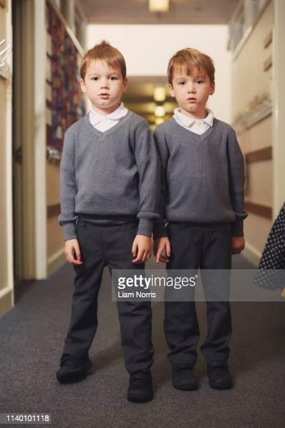 portrait of elementary schoolboy twins in school corridor - schoolboy stock pictures, royalty-free photos & images