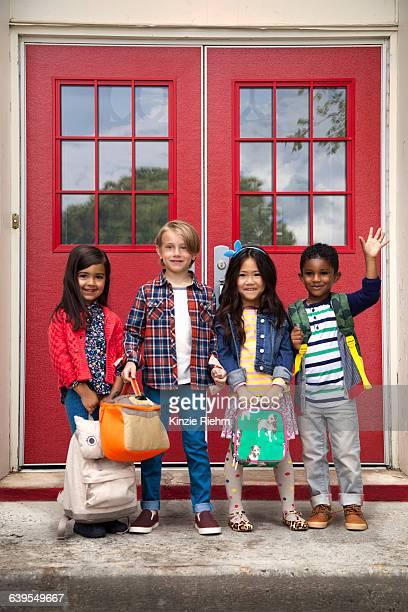 Portrait of elementary schoolgirls and boys waving from elementary school doorway