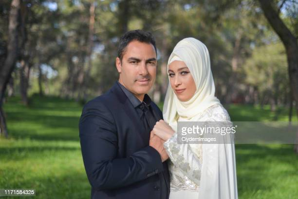 portrait of embraced muslim bride and groom couple looking at camera by holding each other's hands in a public park - honeymoon stock pictures, royalty-free photos & images