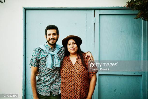 portrait of embracing couple standing in front of blue wall - casal heterossexual imagens e fotografias de stock