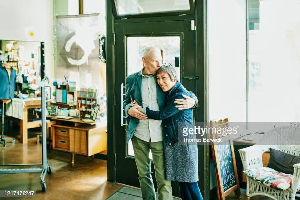 portrait of embracing shop owners in boutique - authenticity stock pictures, royalty-free photos & images