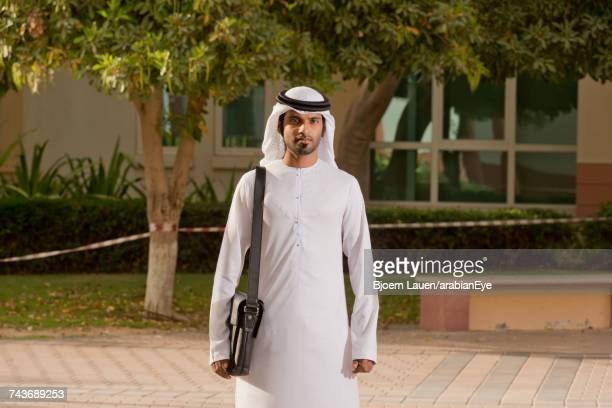 portrait of emirati businessman carrying bag.,portrait of emirati businessman carrying bag. - strap stock pictures, royalty-free photos & images