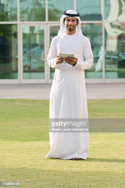 Portrait of Emirati businessman holding digital tablet.,Portrait of Emirati businessman holding digital tablet.